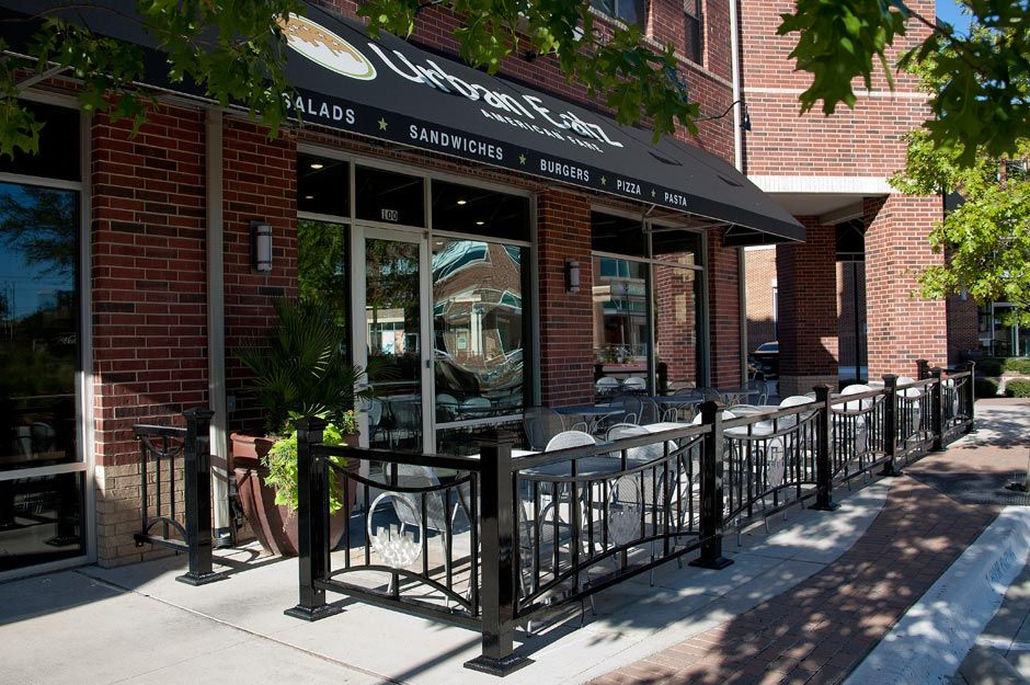 Outdoor cafe seating with metal fencing depicting the logo for Coffee shop exterior design ideas