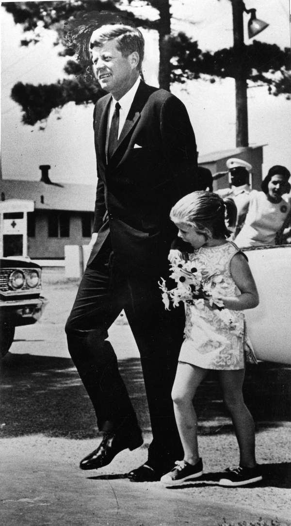CAROLINE KENNEDY holds a bouquet of flowers in one hand and her father's hand in the other as she enters Otis Air Force Base hospital to visit her mother.  -- August 12, 1963