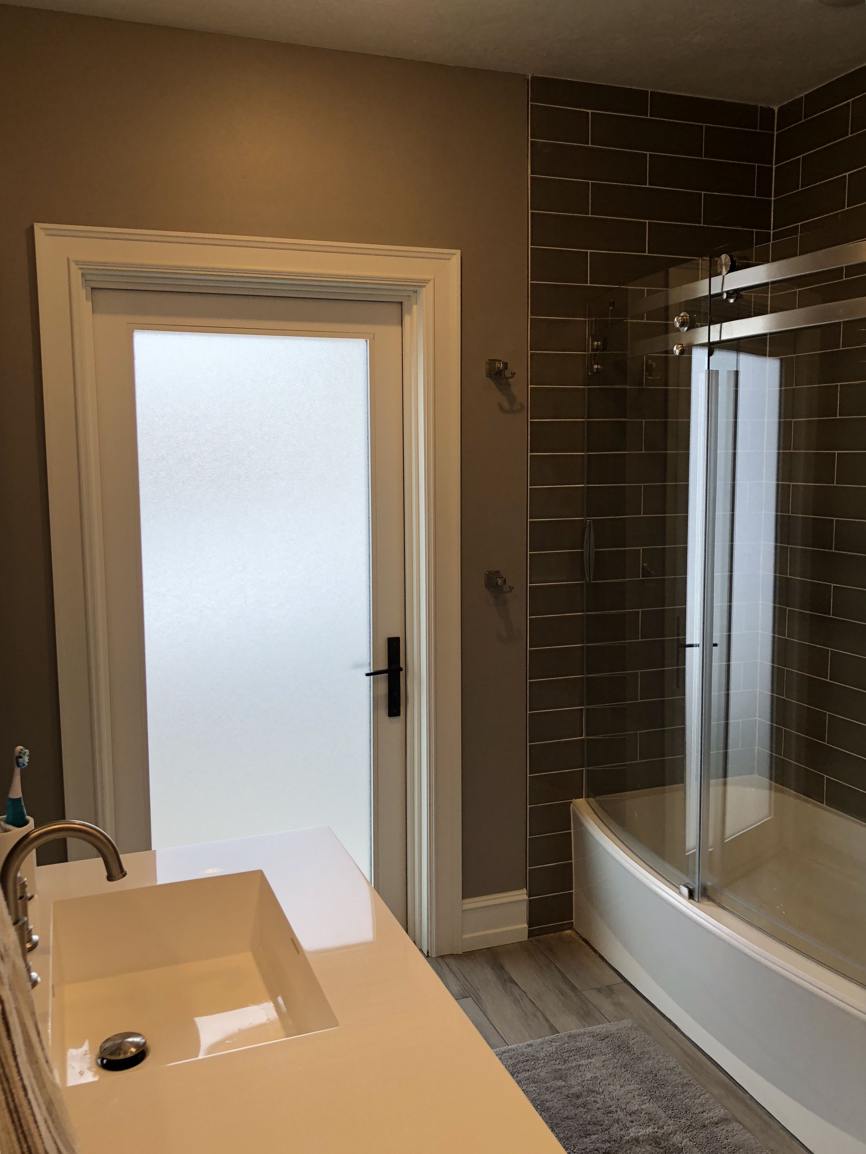 Lower level bathroom with door that leads to backyard/pool ...