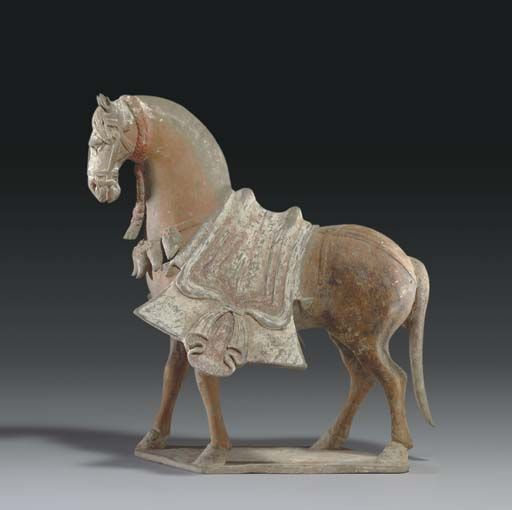 A WELL-MODELLED PAINTED GREY POTTERY FIGURE OF A STRIDING CAPARISONED HORSE -  EASTERN WEI DYNASTY (534-550).