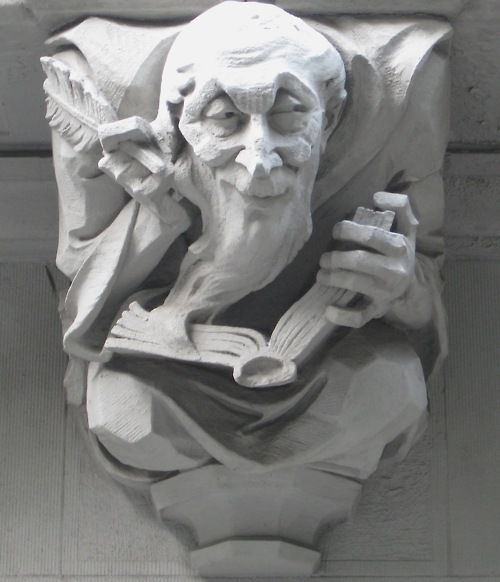 """Grotesque GARGOYLE of a man with a long flowing beard (a monk?) writing in a LEDGER with a quill pen. At THE BRITANNIA (circa 1909), 527 West 110th Street, New York City. The grotesques are meant to symbolize """"some form of the homely art of housekeeping.""""  Waid & Willauer, designers."""