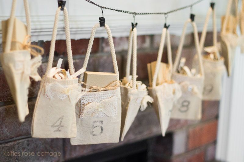 12 days of Christmas little bags hanging on the mantel with a gift inside each. Katie's Rose Cottage - kits are available for sale.