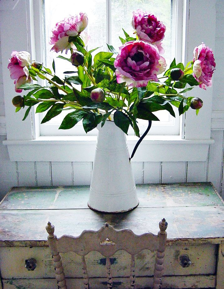 peonies in a vintage french enamel pitcher on an old table in front of the window