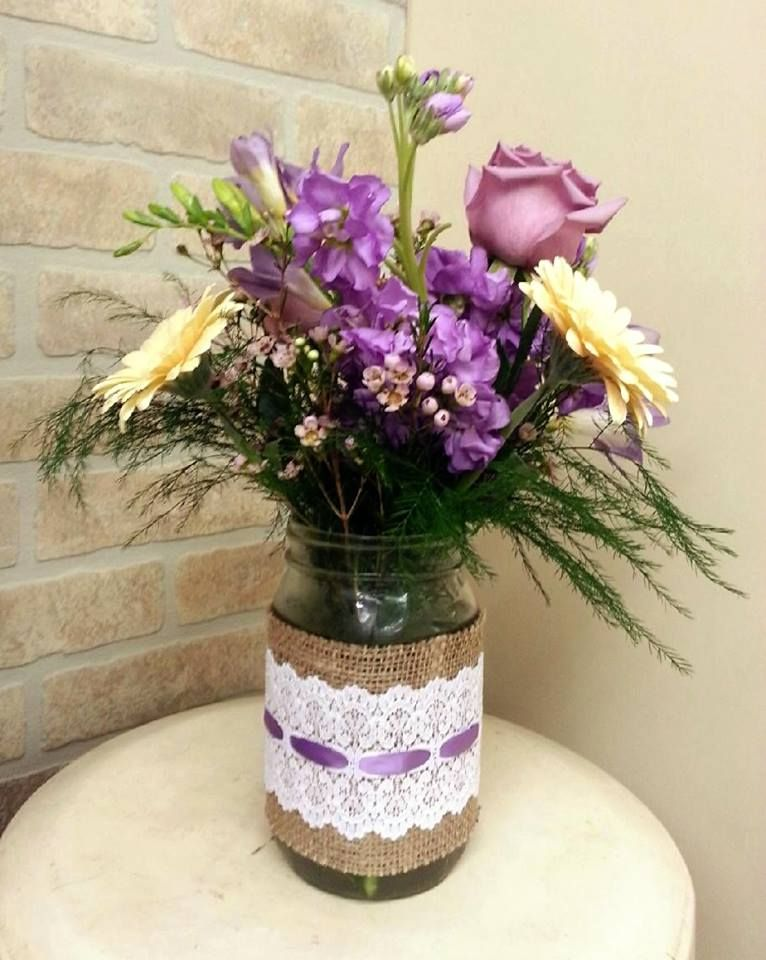 Mason Jar wrapped in Burlap and Lace filled with lavender stock, peach gerber daisies, purple roses and tree fern.  Made by Jane's Flower Shoppe, New Holland, PA