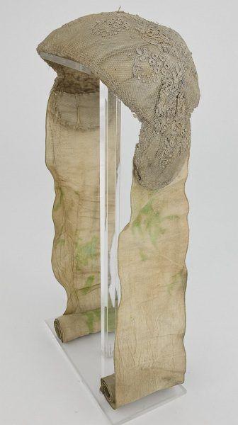 Kleine halbrunde steife Haube mit zungenförmigen Seitenklappen, vermutlich aus Kreis Kellinghusen, mit flauschigem weißen Stoff gefüttert und außen mit weißer glatter Seide bezogen. Bis auf kleines Mittelfeld liegt über weißen Bezug breiter Streifen weißer, industriell hergestellter, an einer Seite gelappter Tüllspitze. Mittelfeld mit einzelnen Blütenzweig in farbiger Petit-Point-Stickerei verziert. An den Seitenklappen sind breite, unverzierte weiße Seidenbänder befestigt…
