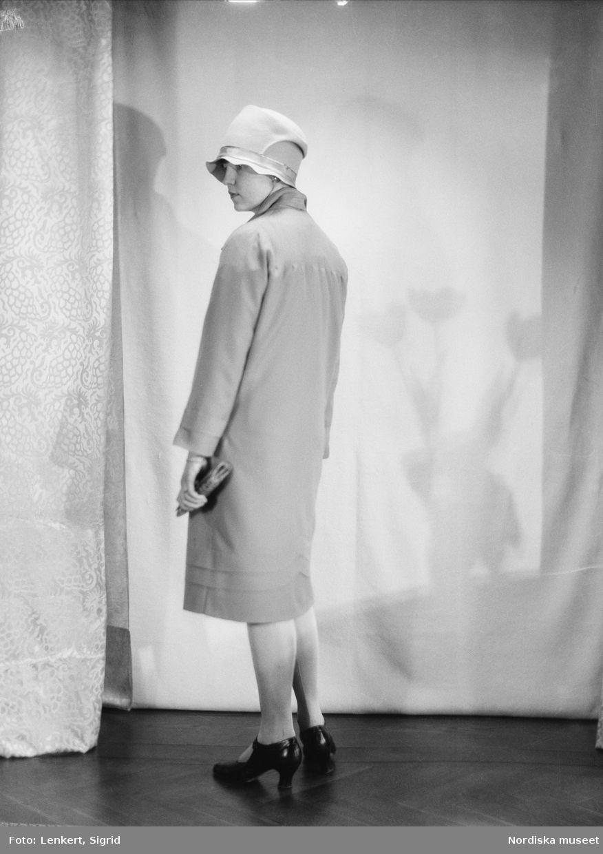 Kvinnlig modell iklädd kappa och hatt. Snett bakifrån. Fotograf  Sigrid  Lenkert 06cf7f207a879