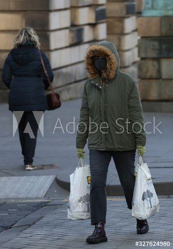 A person wearing a mask walks in the Royal Mile in Edinburgh, Scotland , #AD, #mask, #walks, #person, #wearing, #Edinburgh #Ad