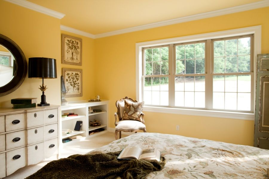 Master bedroom with crown molding a bright yellow wall paint and built in shelves for storage Master bedroom with yellow walls