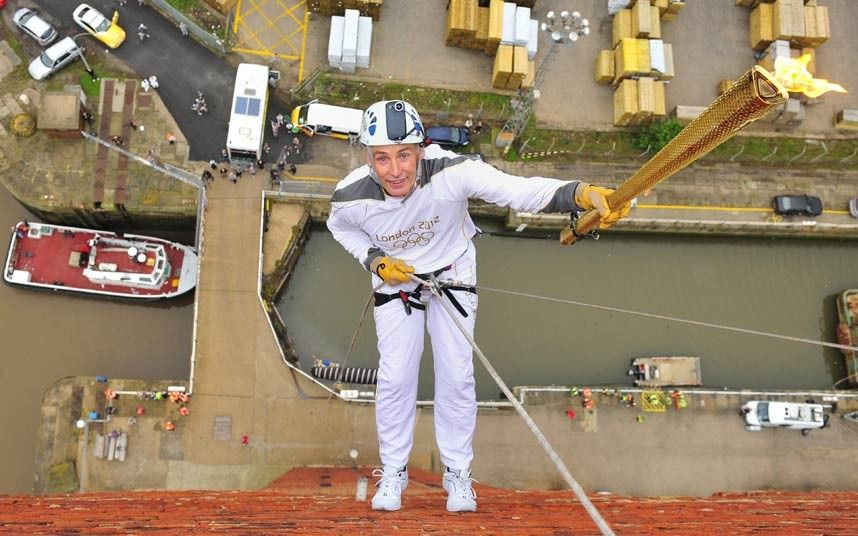 Alan Ellinson abseiling with the Olympic Flame down the side of the Royal Dock Tower in Grimsby (350km north of London) at the beginning of Day 40 of the London 2012 Olympic Torch Relay