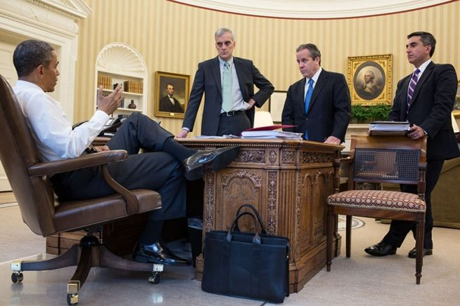 """""""The briefcase you see at President Obama's feet in the official White house photo above, propped gently against the legendary Resolute Desk, is Frank's Double Gusset Zip Top Briefcase, in black harness belting leather."""""""