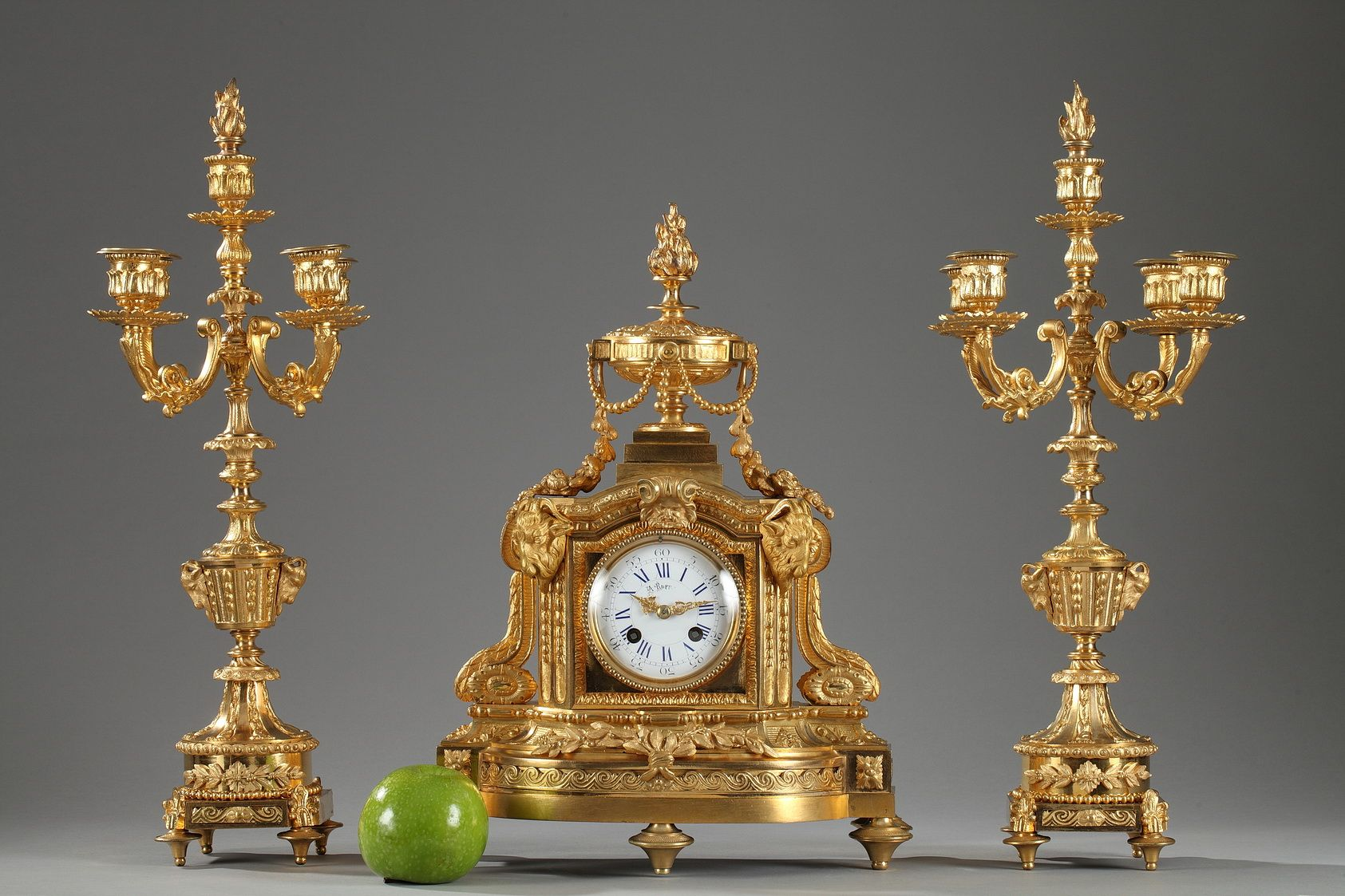 A gilt bronze set in Louis XVI style richly chiseled with ram's heads, foliages and garlands of flowers, composed of a mantel clock and two candlesticks. The white enameled...