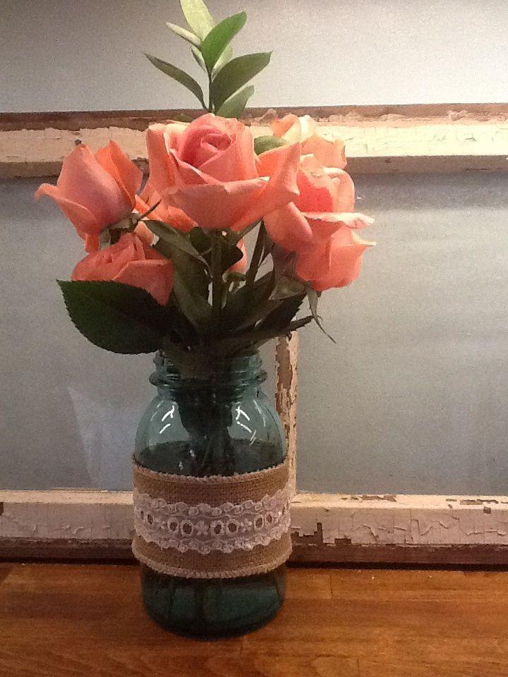 Blue mason jar , burlap with lace sleeve, pink roses.