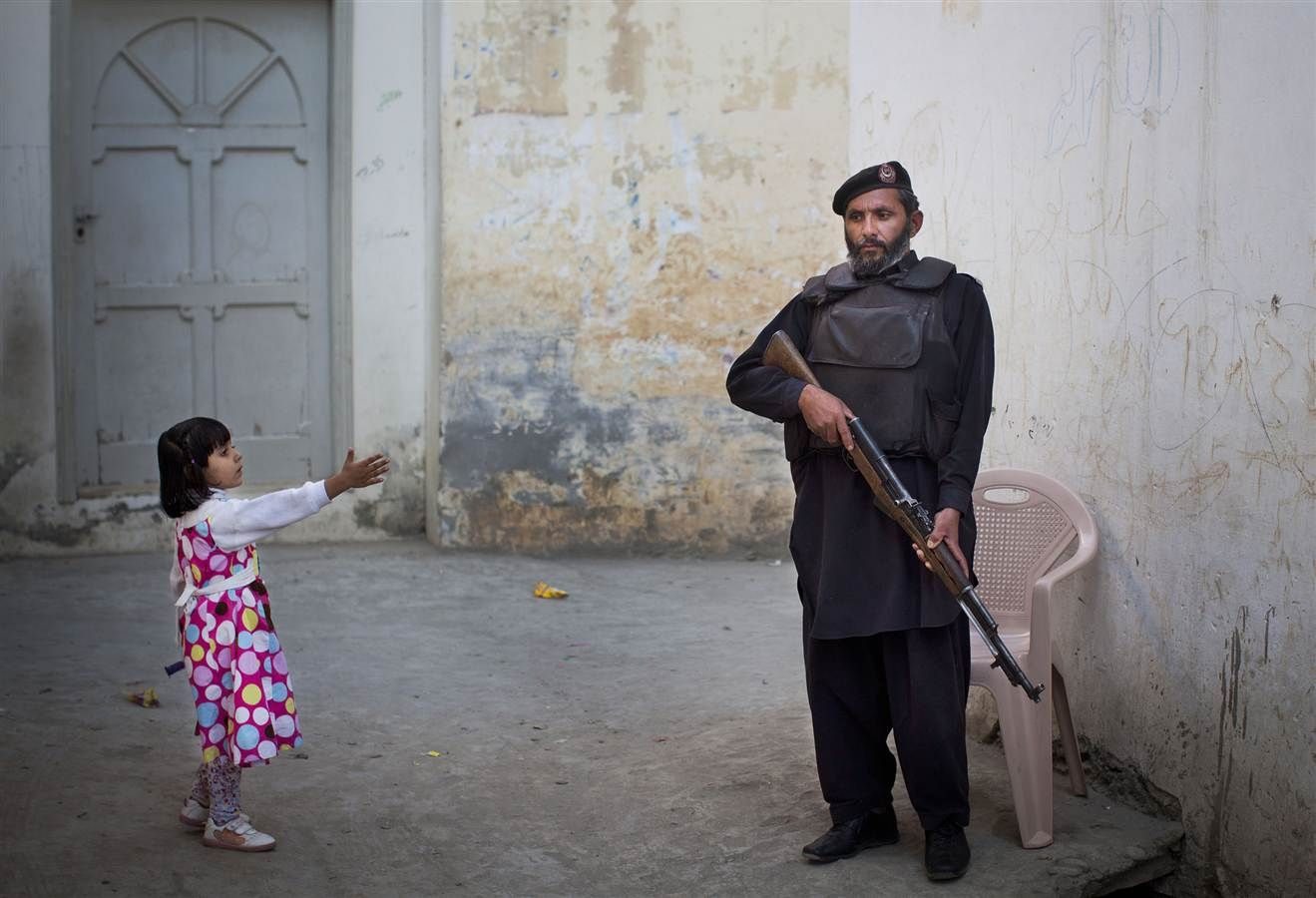 anja niedringhaus.....a young girl reach out to greet a pakistani policeman