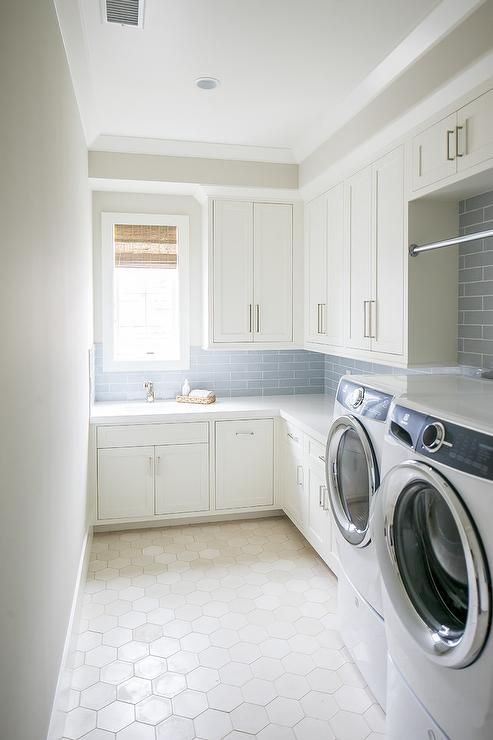 A White Front Loading Washer And Dryer Sits On Large White Hex