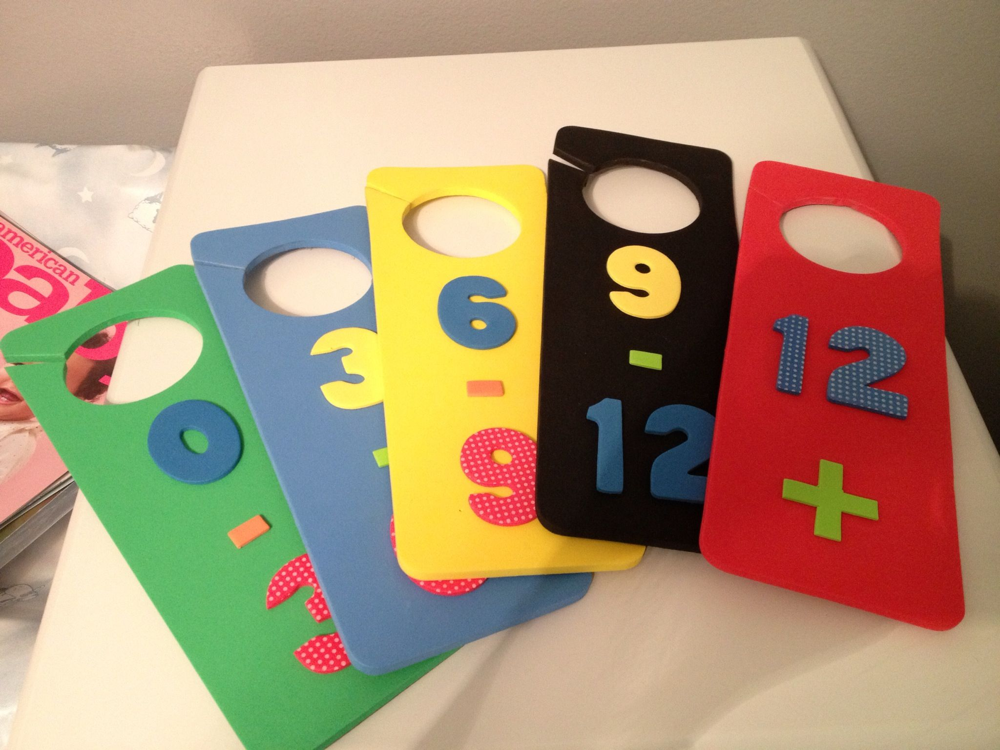 Inexpensive closet dividers  Foam door hangers with numbers pasted on both sides.