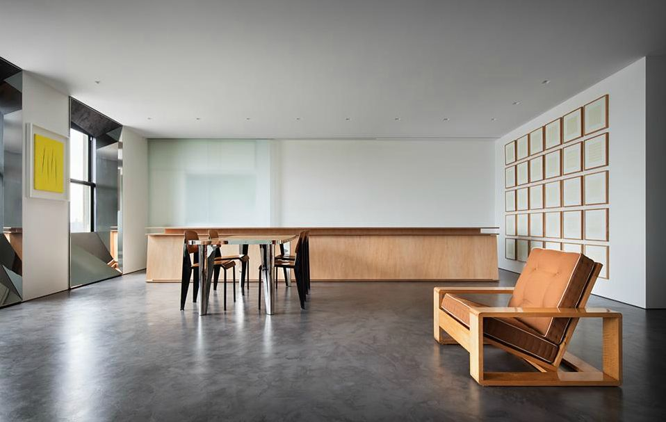 Kitchen. Fifth Avenue Apartment. Mirror-polished stainless steel surrounds by windows, concrete flooring, maple-veneered plywood island, sliding panels hide appliances, Jean Royere chair. Architect: Thomas Phifer.