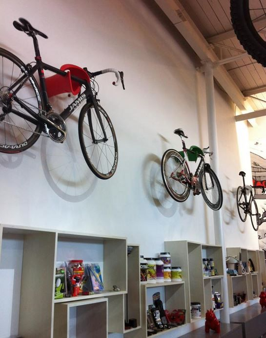 Got High Ceilings Hang Your Bike Above A Bookshelf For Extra Efficiency Clever Space Design Bike Storage High Ceiling Design