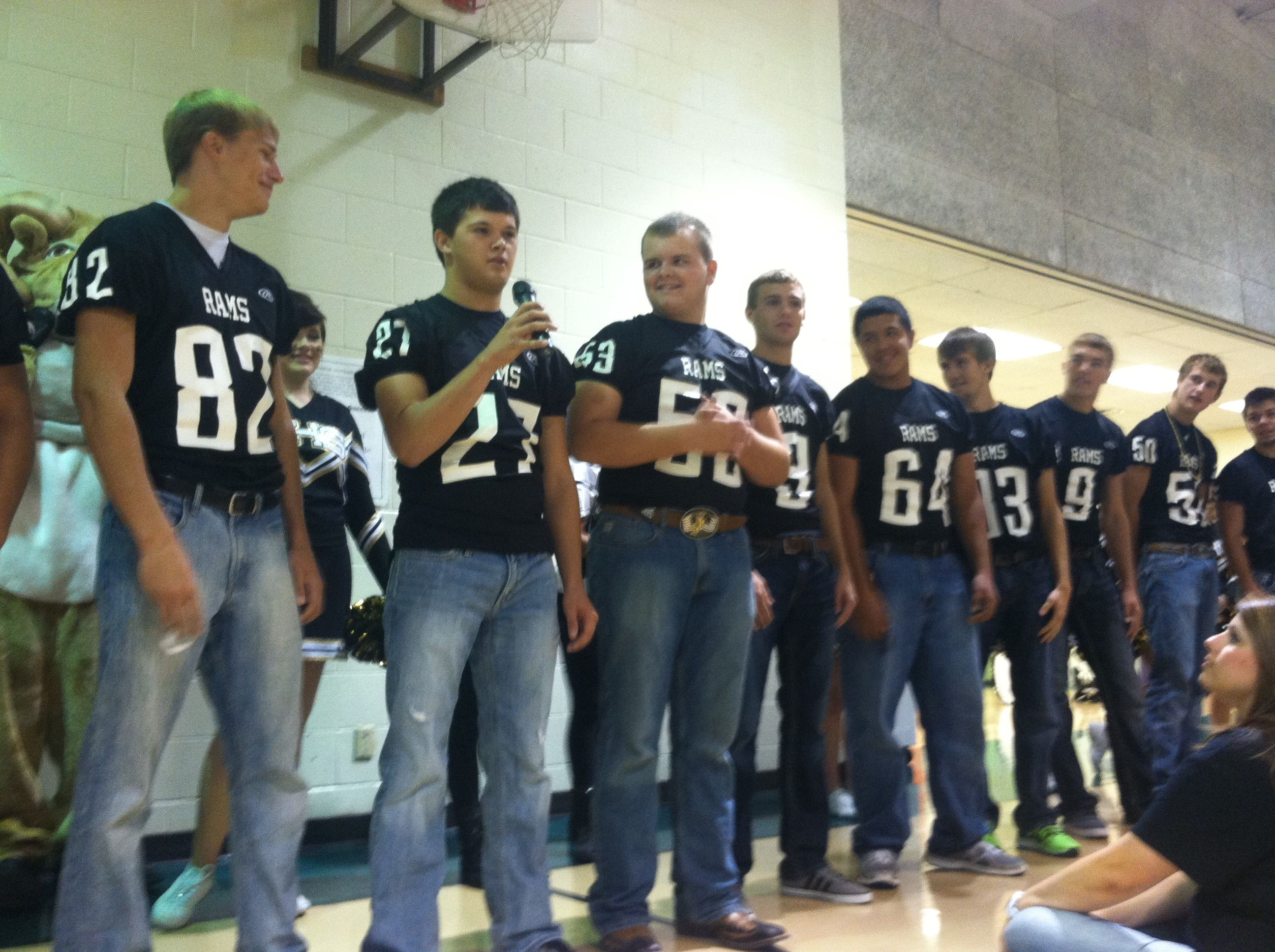 Senior football players talk to elementary kids at their
