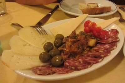 Italian antipasti dish; easy starter to make with some tasty hard Italian cheeses, good quality olives and different kinds of Italian salami. Finish with the soft caponata in the middle; recipe on my blog.