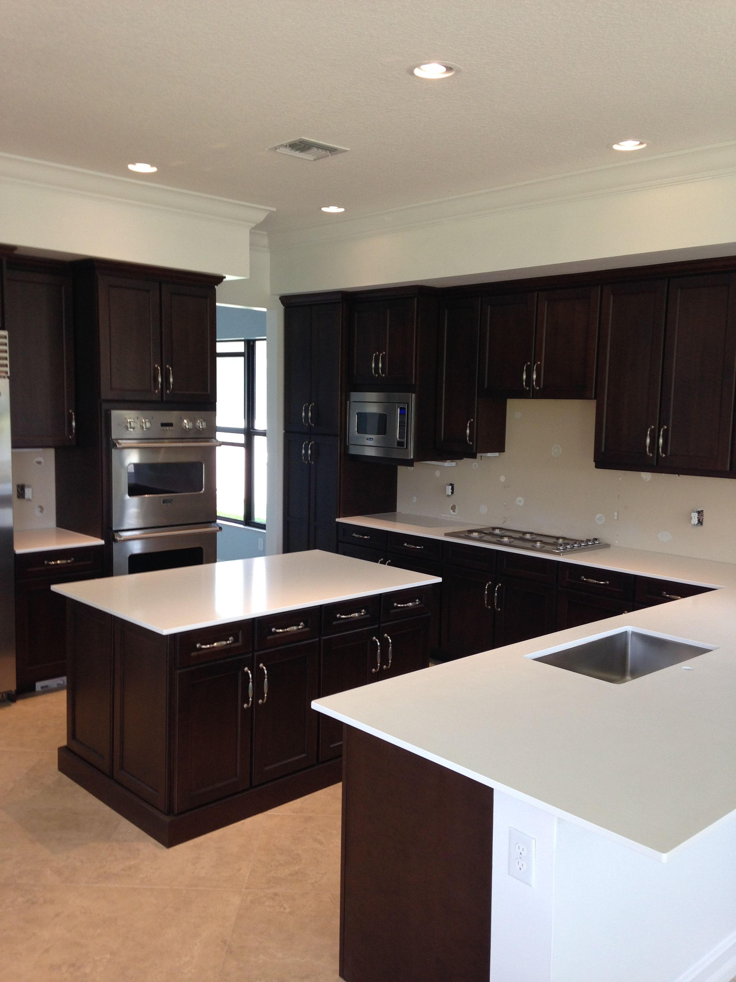White Quartz Countertops And Brown Dark Cabinets Http Www Stoneandquartzsurfaces Com Qu Dark Brown Kitchen Cabinets Brown Kitchen Cabinets Brown Kitchens