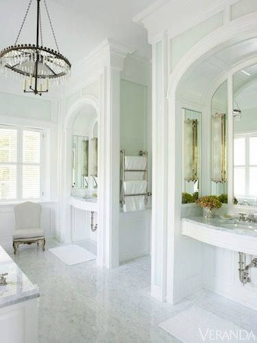 This luxurious Master Bath uses classical architectural features from ceiling to floor.The marble floors & counters add to the regal design.Separate sinks w/ wall dividers give privacy & grandeur. There must be many windows for this to be so flooded w/ natural light.