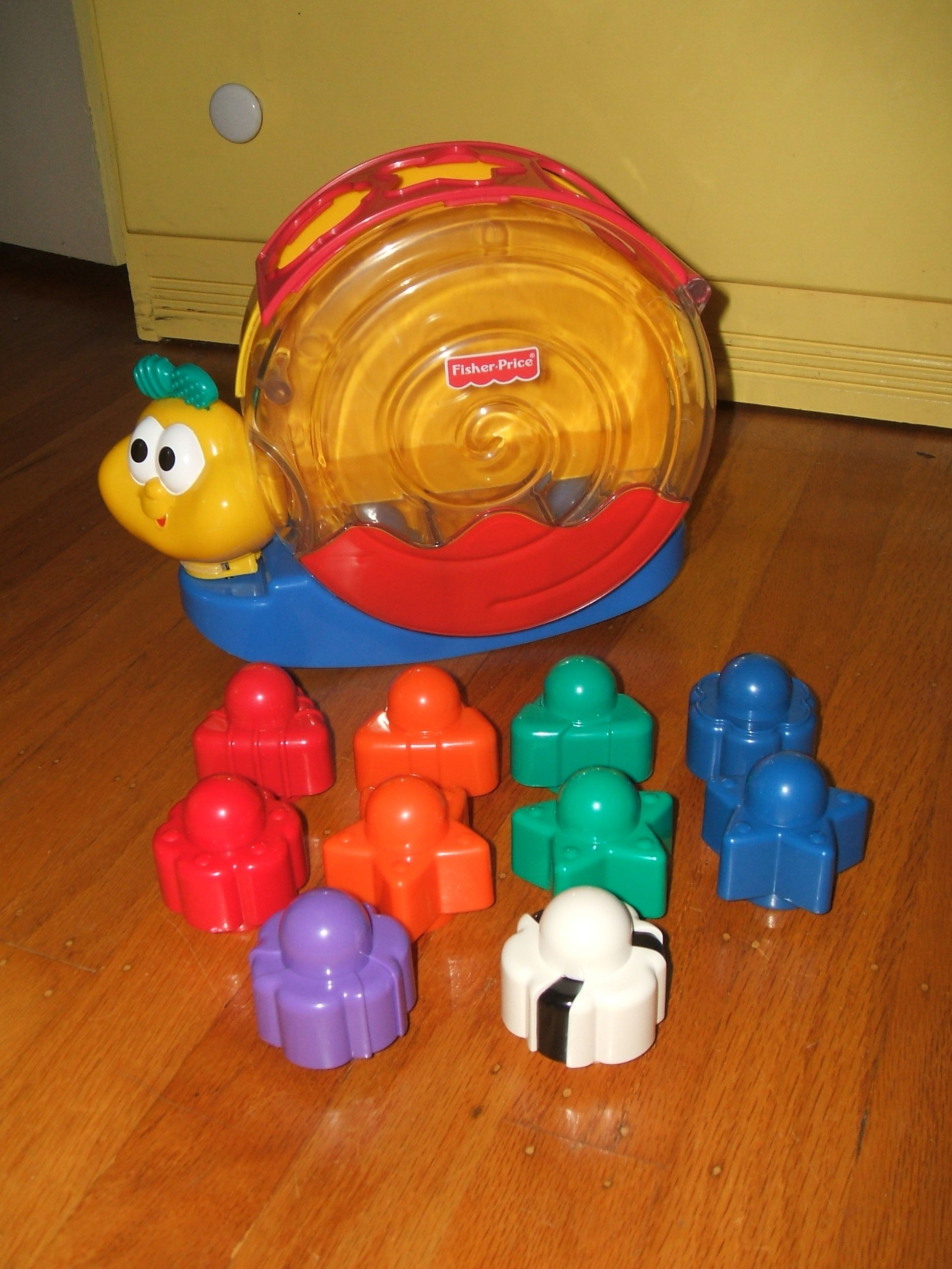 Fisher Price Singing Snail Pail And His Set Of 10 Stack And Posting Blocks Rock Him A Little Ad He Plays A Happy Litt Fisher Price Toys Cute Toys Fisher Price