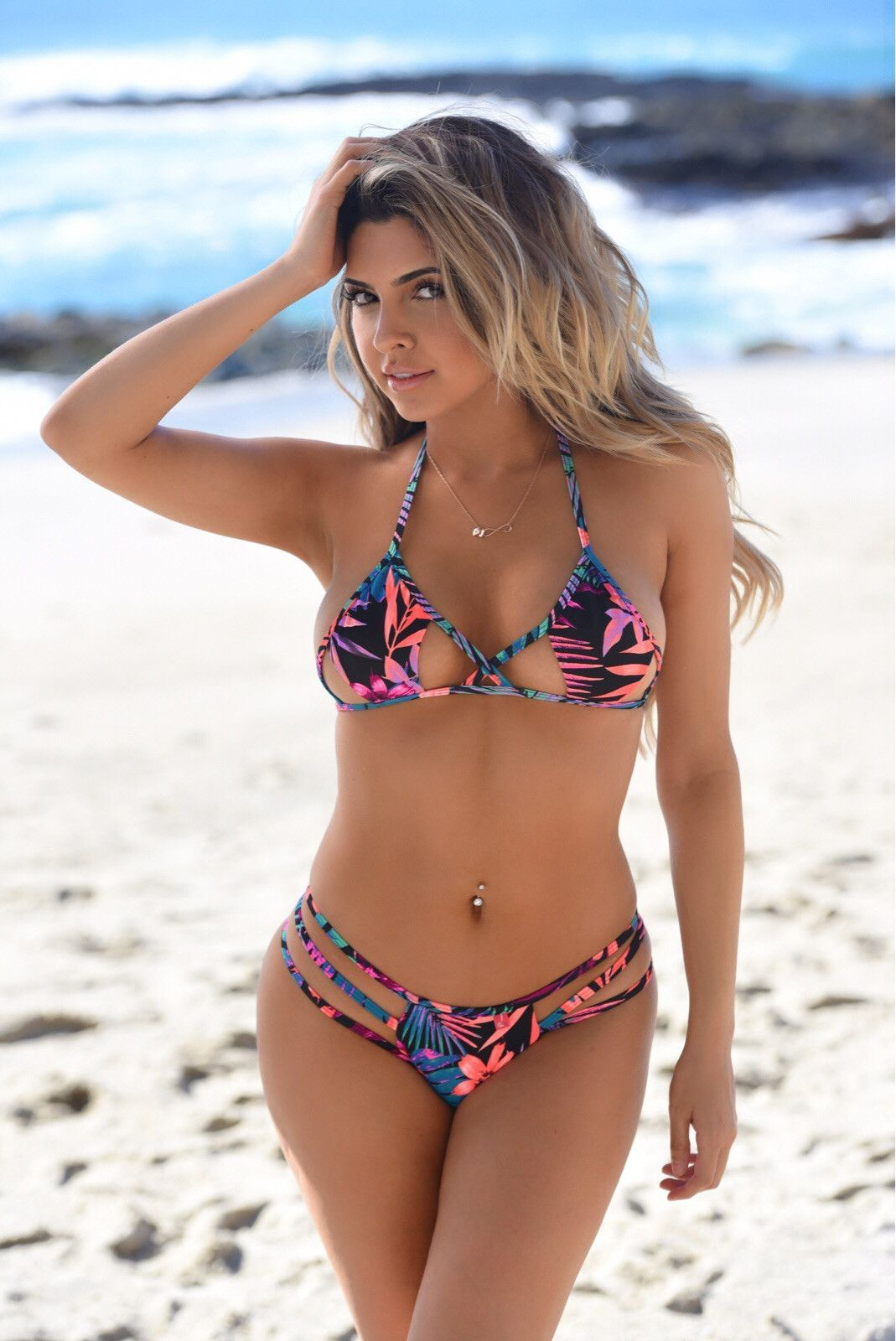 33cfc2b92f33b Mrytle Beach  This bikini is a triangle top with cut-out detail. Paired  with a strappy thong bottom in Orange Tropical. Also available in other  colors.
