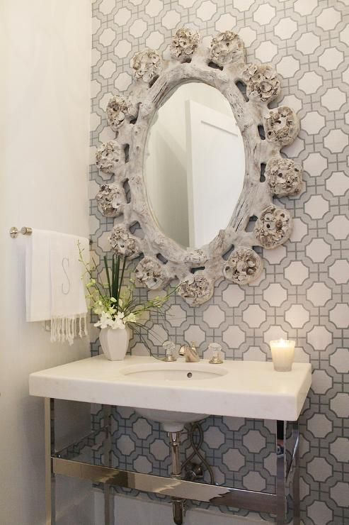 Chic, gray powder room features an accent wall lined with gray geometric wallpaper, Phillip