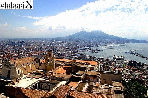 Napoli - Il Vesuvio visto da Napoli-   Il Vesuvio, vulcano ancora oggi attivo, si presenta come un monte bicipite con l'insellatura tra le due cime a ca. 700 metri sopra il mare. La cima sinistra è il monte Somma (1130 metri) e la cima destra è il Vesuvio (1280 metri).  Fotografo:Marco Arrigoni
