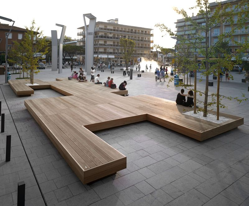 A Large Bench Serves As A Gathering Place In This Town Square