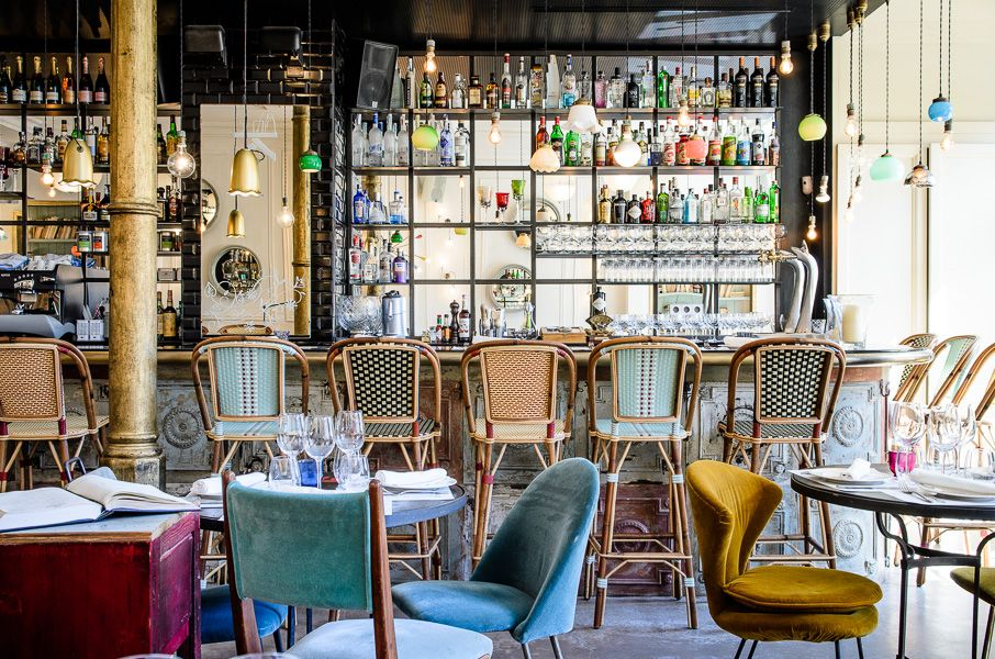 stunning cafe in Barcelona, Spain- chairs covered in velvet, black and mirrored walls, woven French bistro bar stools and a plethora of pendants