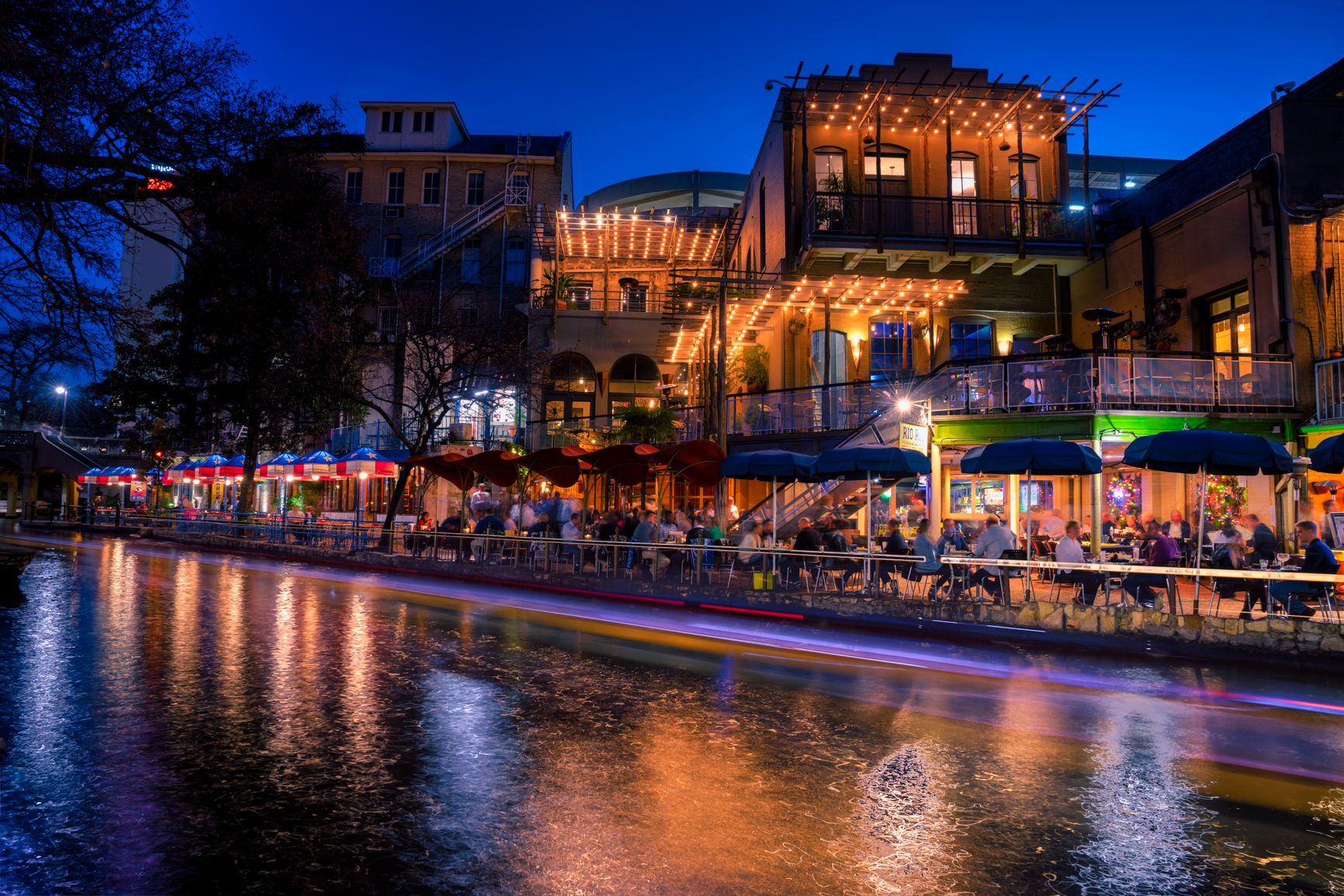 A Riverboat Passes In Front Of Some Restaurants Along The