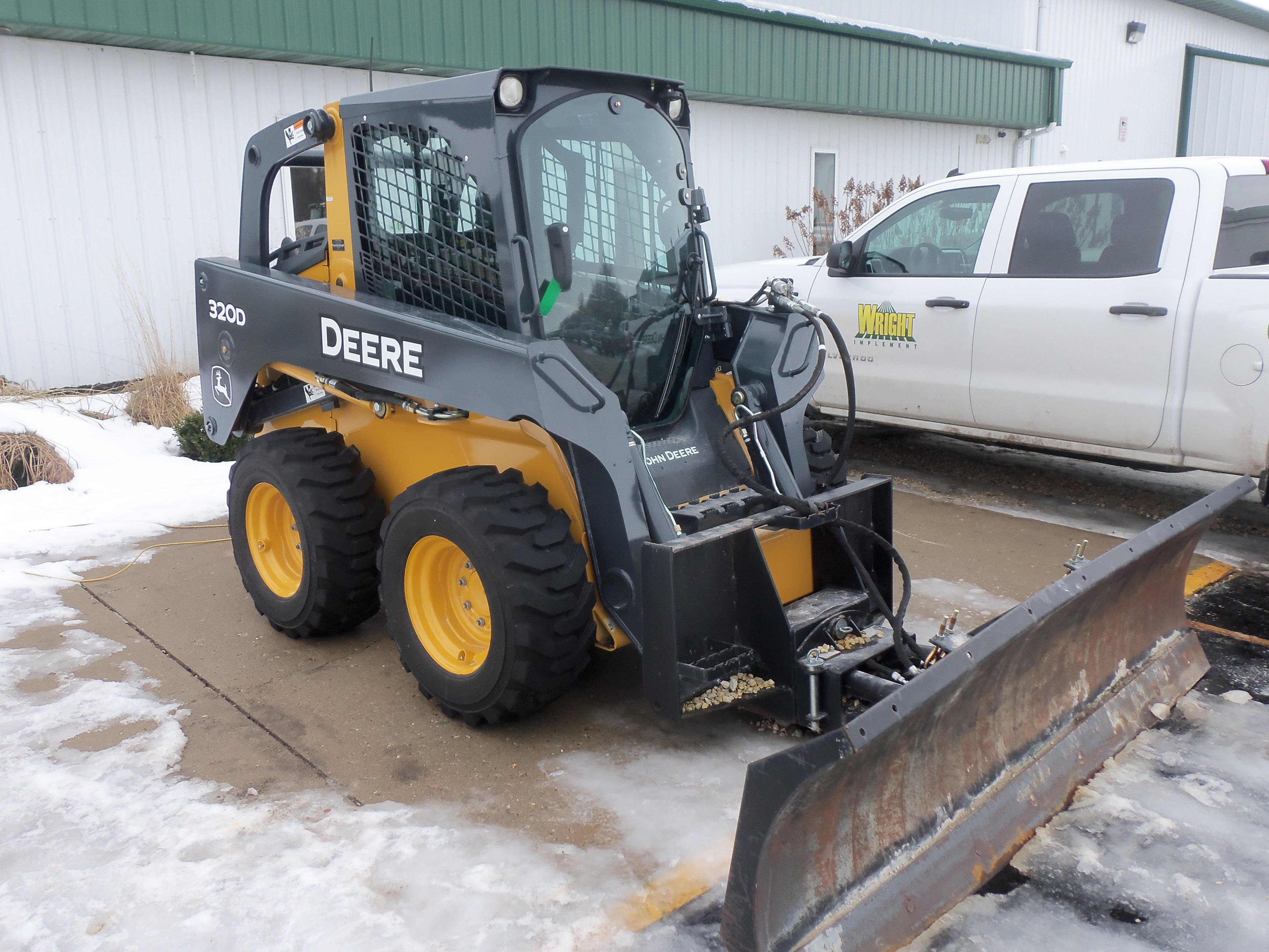 John Deere 320D skid steer loader with snow plow blade.Saw this at Wright  Implement in Crawfordsville