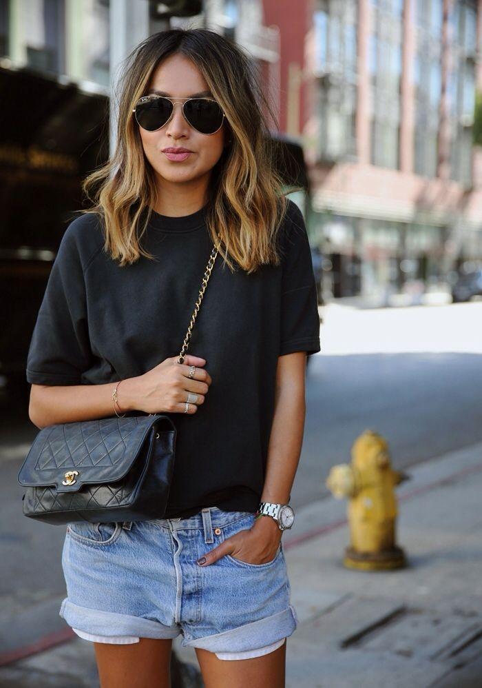 schwarzes T-Shirt mit einem Rundhalsausschnitt, hellblaue Jeansshorts, schwarze gesteppte Leder Umhängetasche, schwarze und goldene Sonnenbrille für Damen