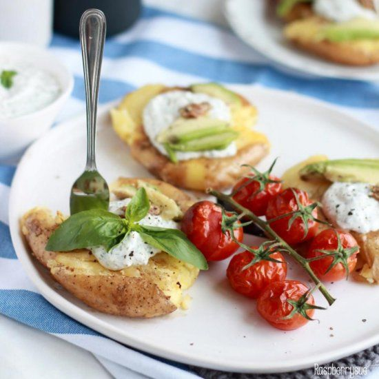 Delicious summer food - crushed potatoes with oven-roasted sweet tomatoes, creamy feta dip, avocado and basil
