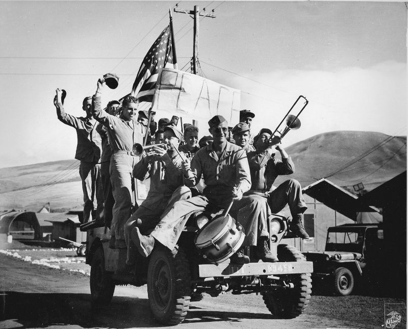 Marines 5th Division celebrate Japan's surrender, climbing on a jeep with musical instruments, the United States flag and a homemade banner with the word 'Peace' ('Peace'). The island of Iwo Jima.