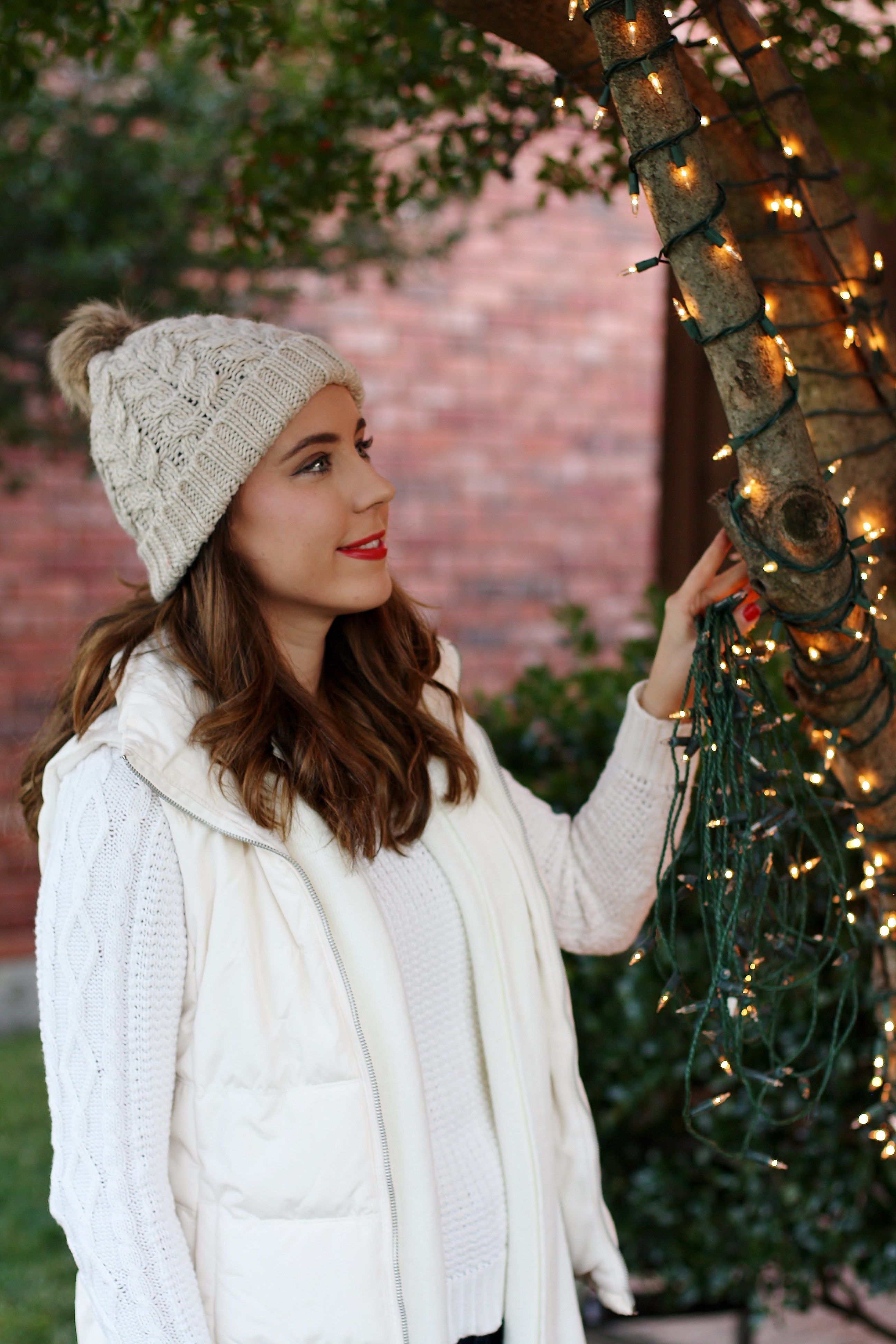 hanging the christmas lights faux fur pom beanie white cable knit sweater puffy vest white scarf holiday style winter fashion winter outfit