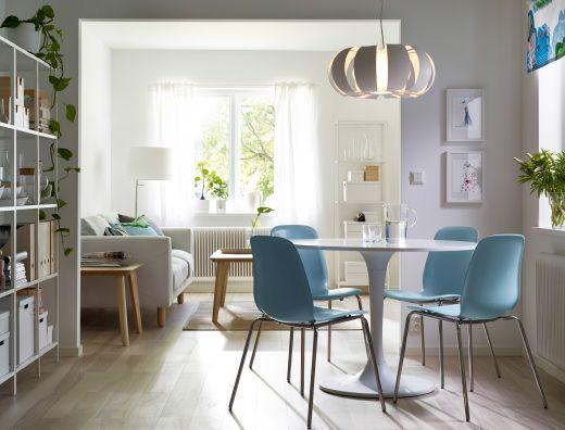 Un comedor con una mesa blanca redonda y sillas en azul claro con patas de acero inoxidable.