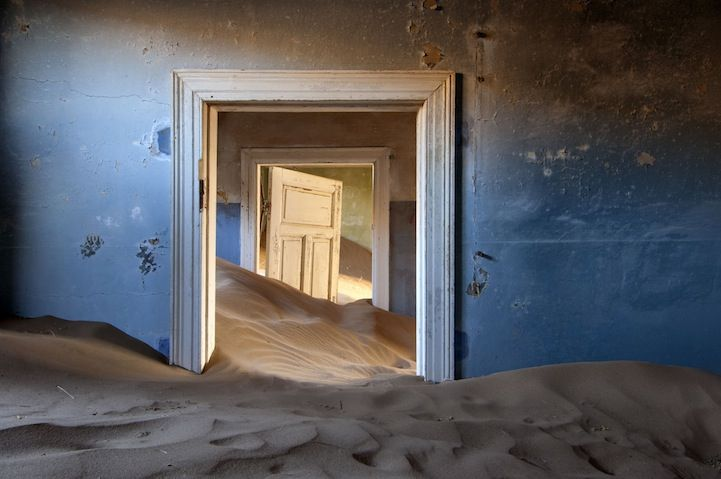 Namibia | In a scene stolen from a dream, a house succumbs to sand in Kolmanskop, once a thriving settlement for diamond miners. Winds have helped desert dunes reclaim the site, abandoned for more than 50 years. Photo by Marsel Van Oosten. ©2011 National Geographic