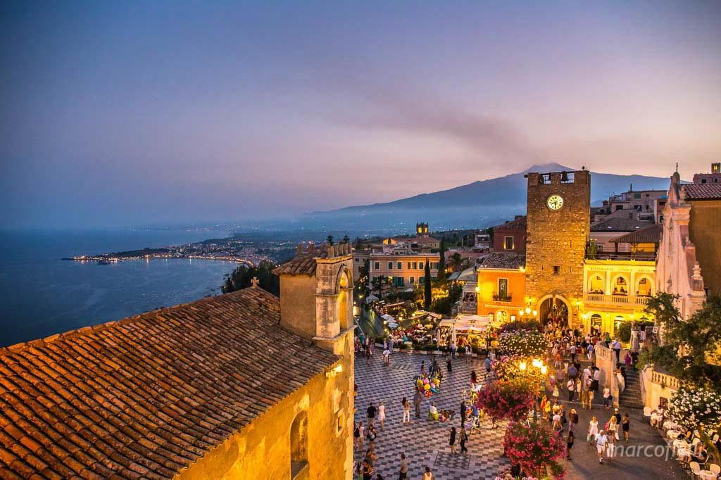 Sunset view of Taormina. The clock tower and the mount