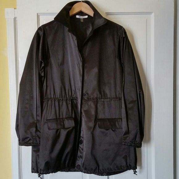 DKNY Jacket Black jacket with drawstrings at waist and at bottom hem, roomy pockets and snap buttons. Can be worn casually or dressed up. Collar can be worn down or up trench-style. The material has a slight sheen. DKNY Jackets & Coats