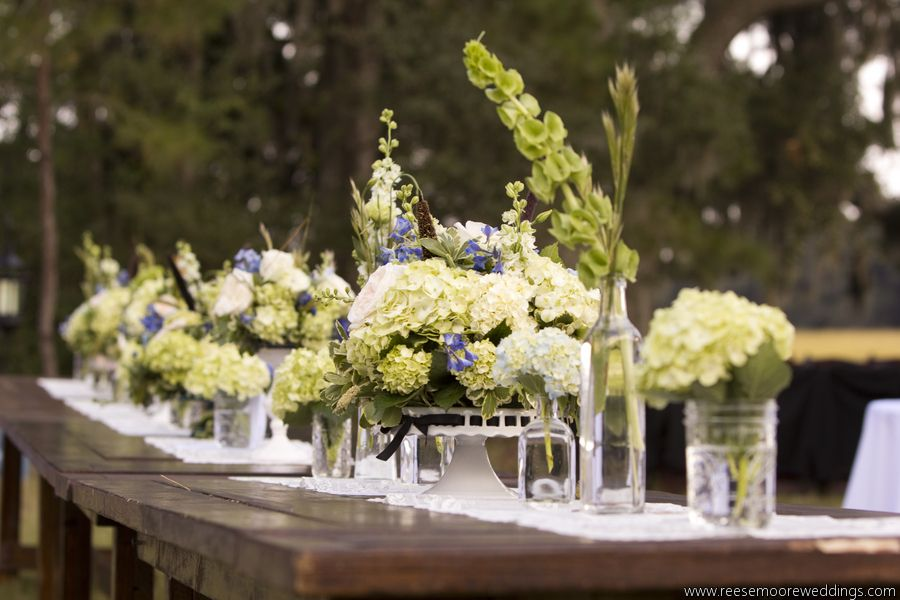Vintage pie plates, mason jars and apothecary bottles with hydrangea, delphinium, grasses, Belles of Ireland, garden roses and larkspur.