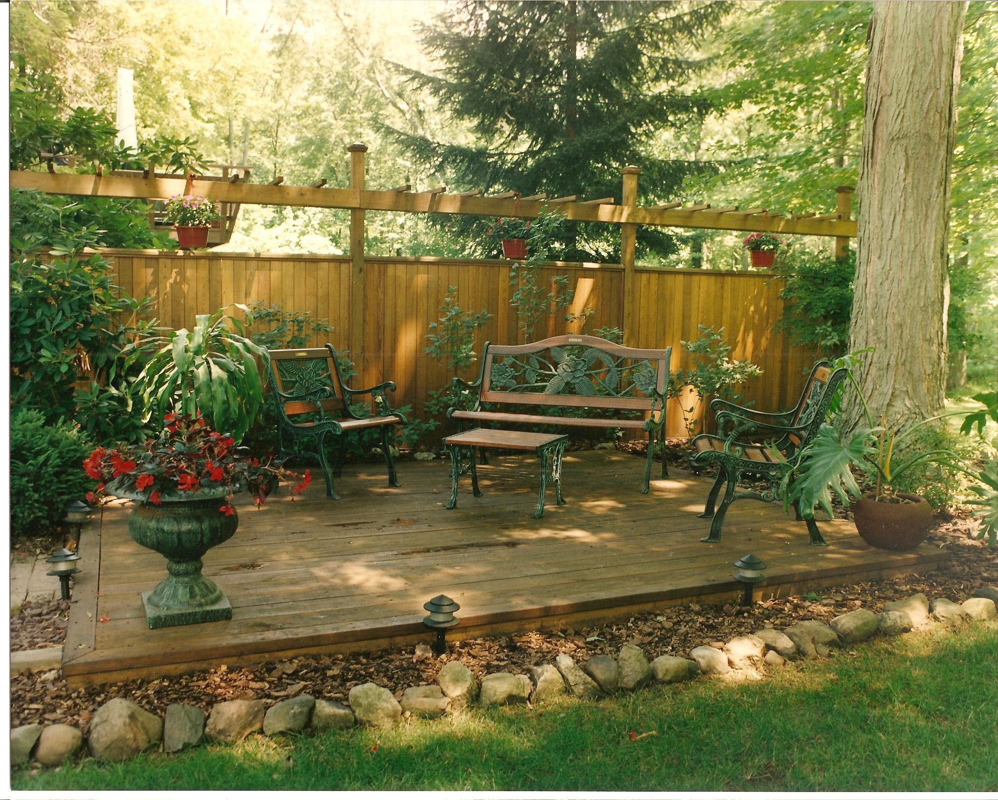 Backyard privacy wall with deck attached landscaping for Garden decking borders