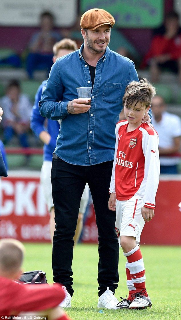 Proud father: The promising footballer got a hug from his dad David during half time...
