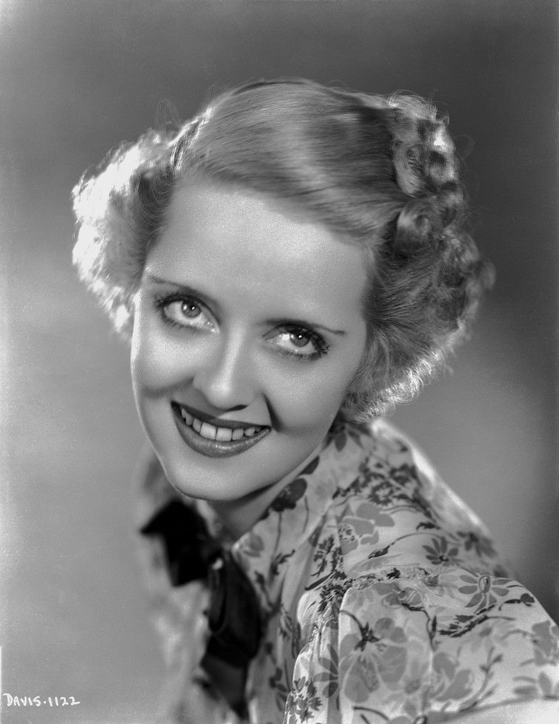 Bette davis portrait in looking up in floral dress with top knot and