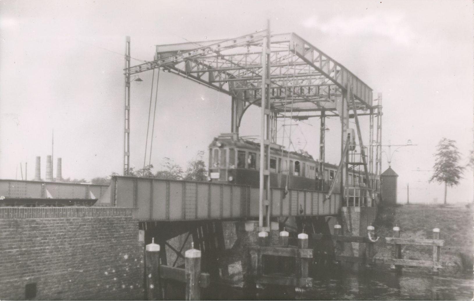 Gezicht op de trambrug over de Trekvliet nabij de Lammeschans met een zogenaamde Boedapester tram (NZHTM-lijn Leiden-Voorschoten-Voorburg-Den Haag). Links op de achtergrond de kalkovens aan de Zoeterwoudseweg (ca. 1955).