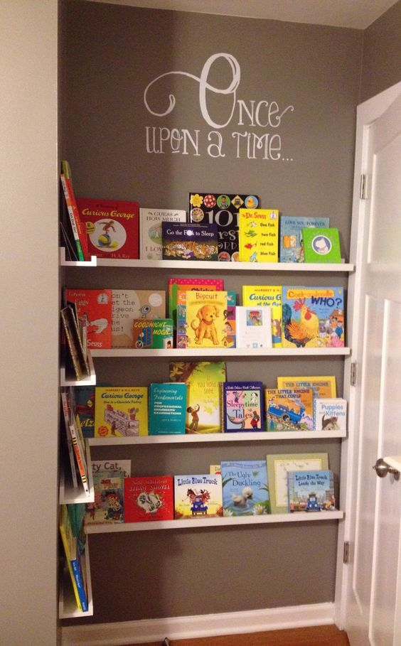Book nook in other wise unused space. Cheap photo ledges from IKEA   etsy wall decal = custom nursery library