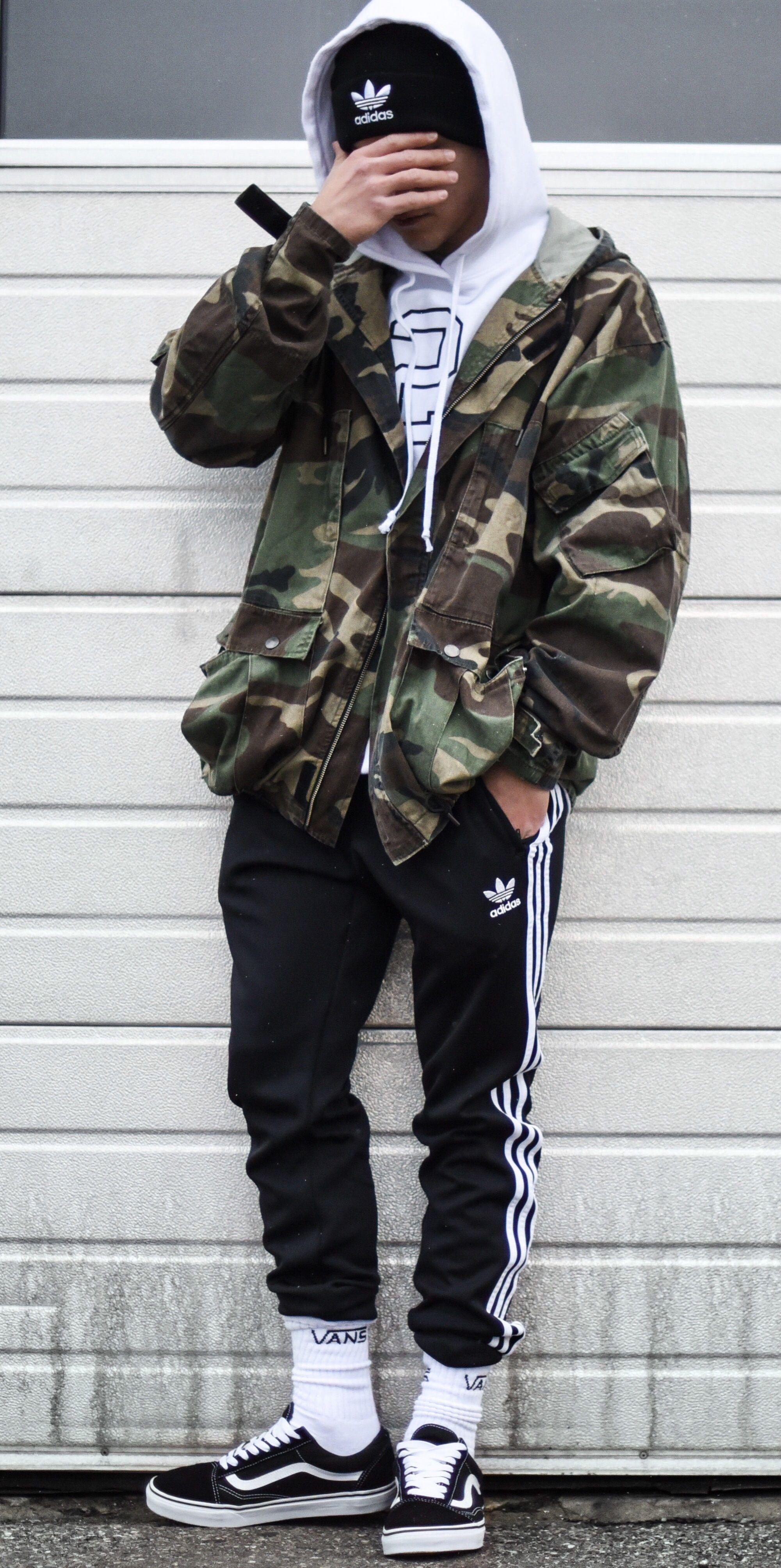 dc907c56df ... bem urbano com essa jaqueta militar sobrepondo uma camiseta branco de  capuz sobre a toca preta. Pra deixar a roupa ainda mais estilosa essa calça  Adidas ...