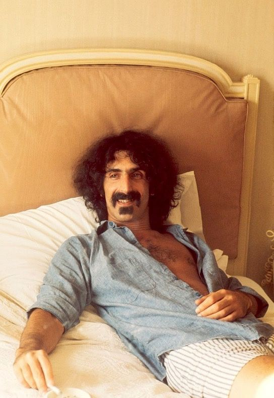 Frank Zappa photographed by Michael Putland in his hotel room in London, 1973.