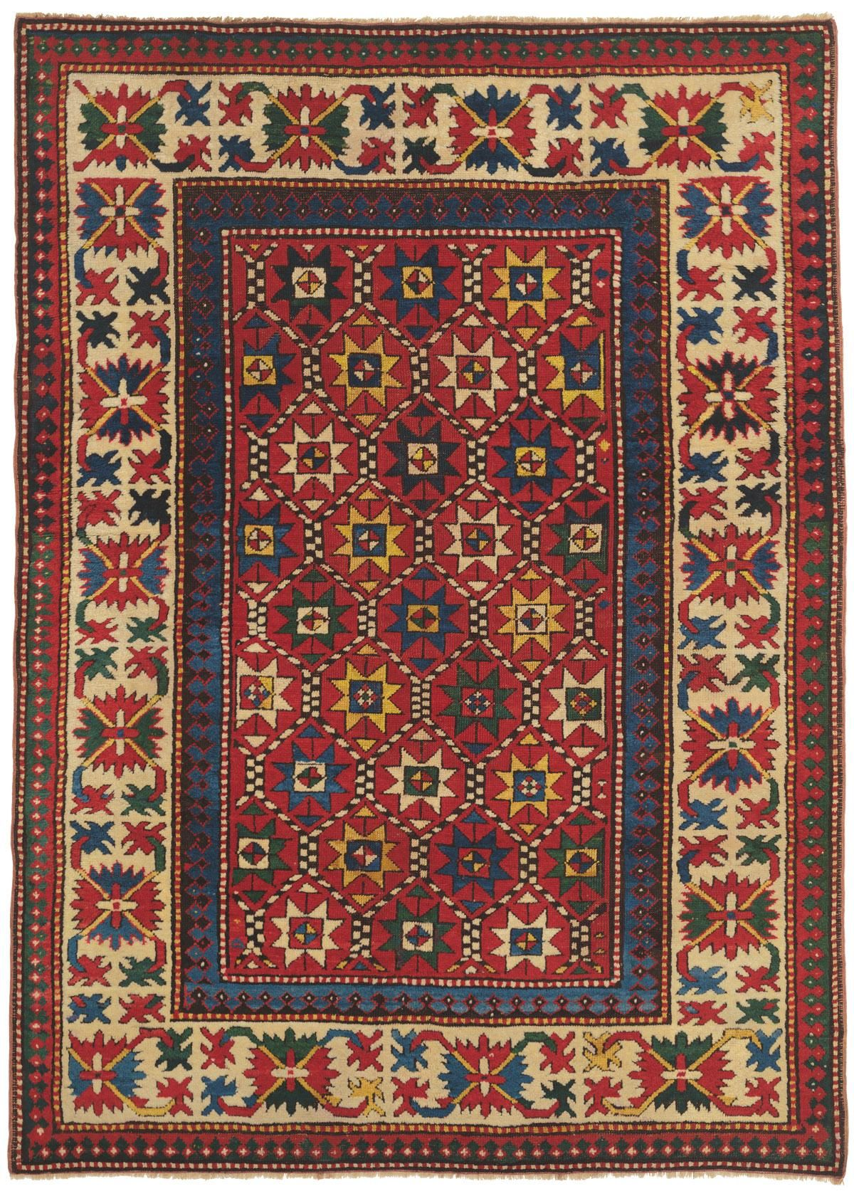 Caucasian Kazak, 4ft 8in x 6ft 6in, Circa 1900. Masterful use of color and dazzling elemental motifs bring a folkloric appeal to this collectible Kazak rug. A riveting palette that includes prized saffron yellow, radiant cobalt blue, clear ivory, azure and forest green energizes each dynamic sunburst-like 'Star of Wisdom' on the deeply saturated carnelian red ground. The deft use of abrash striation, most notable in the inner border, adds a luminous depth to the composition.